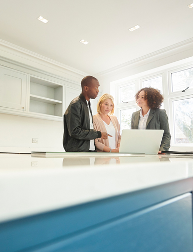 couple having a discusson with their real estate agent in front of a computer